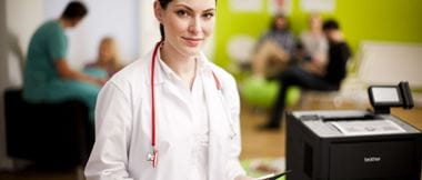 A female doctor is wearing a traditional white medical coat with a stethoscope hanging around her neck. She's standing in a hospital waiting room with patients and healthcare staff in the background. She is standing next to a Brother multi-function business printer.