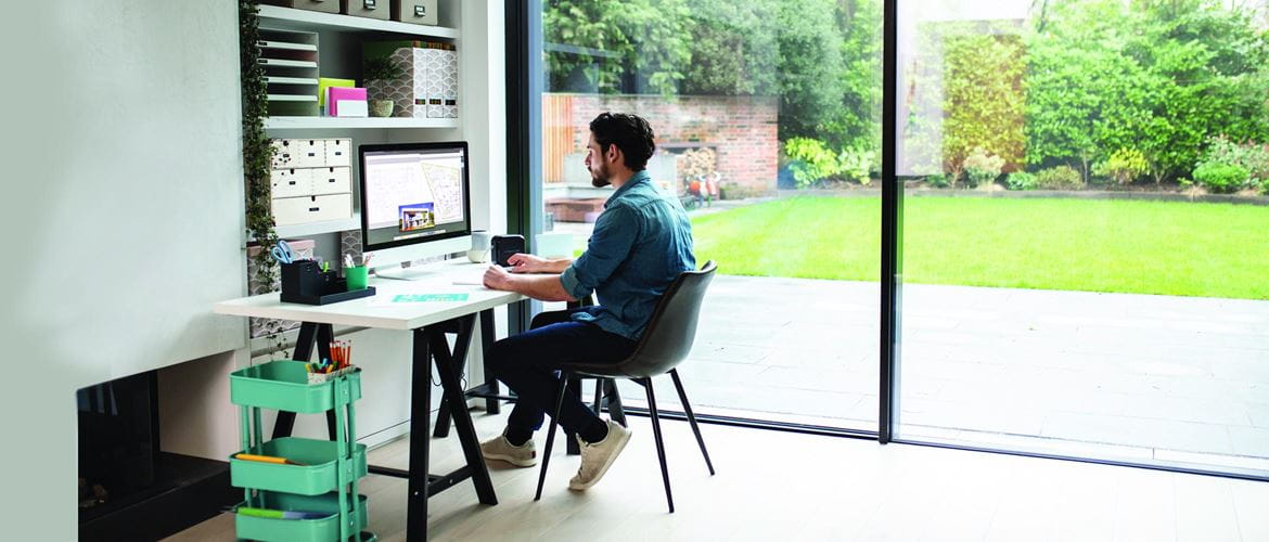 A male staff member is working from a home office / hybrid working. He is sat at a desk working on a desktop computer with a Brother P-touch labelling printer at his side to increase business productivity.