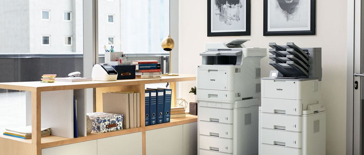 Two floor standing printers side by side against wall in office, cabinets, folders, windows