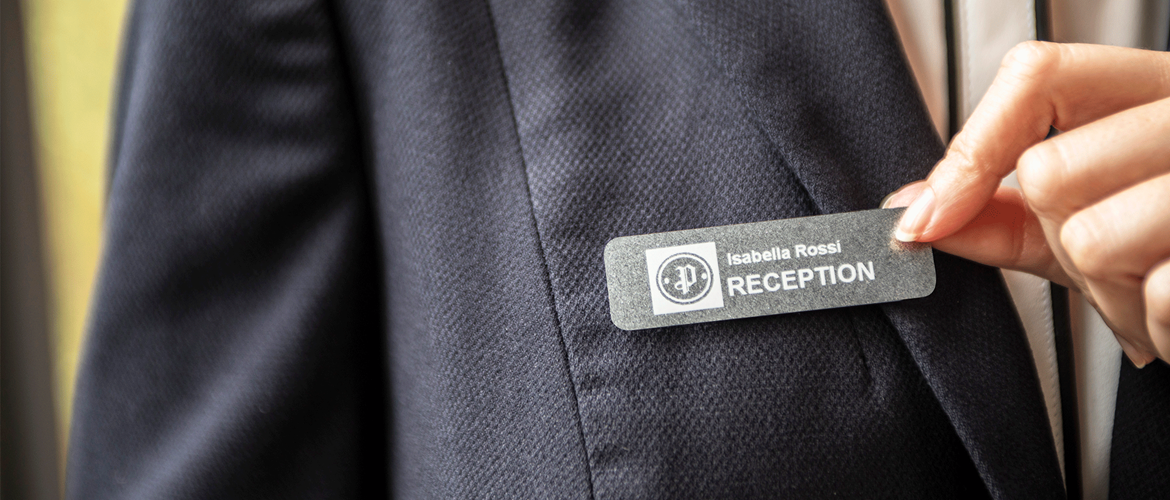 Receptionist wearing name badge made from Brother device