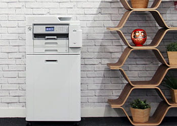 Printer on cabinet against grey brick wall next to hexagon shelving, plants, vase
