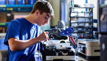 Man in blue tshort with tools working on a printer on a work bench