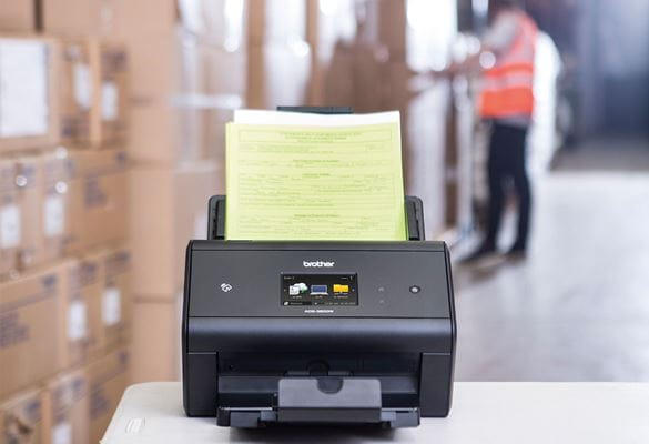 Brother ADS-3600W desktop scanner on table archiving dispatch notes in a warehouse, boxes, man in hi-vis