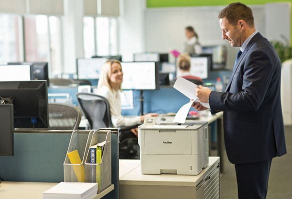 Man wearing suit standing at printer holding paper, monitors, woman, office, table