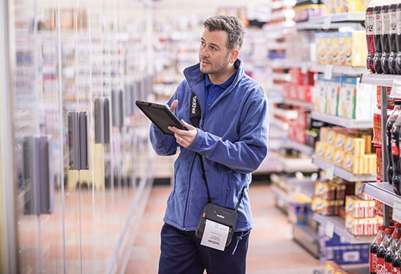 Direct store delivery agent checking clipboard in grocery shop with Brother RJ-4 printer on shoulder strap