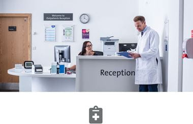 Hospital reception with female receptionist talking to doctor in white coat and grey clip board icon