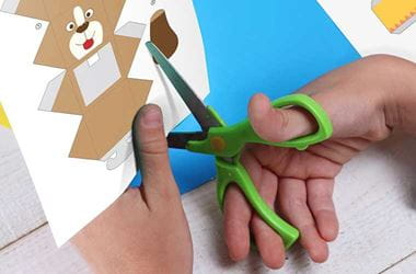 Child using scissors cutting out picture of dog