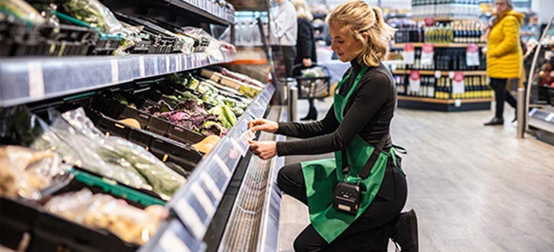Female wearing green apron in supermarket kneeling down labeling shelf