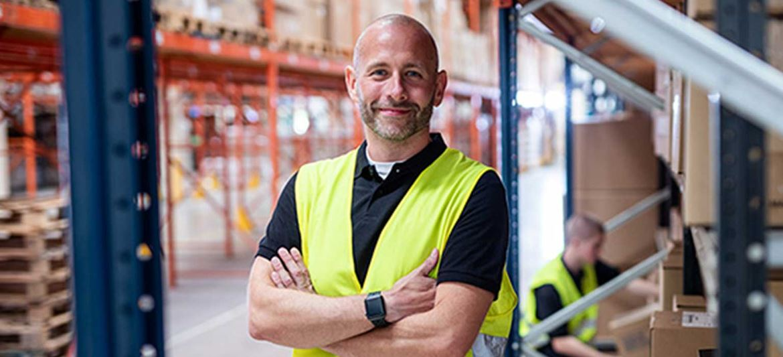 Man smiling wearing hi-vis vest in warehouse