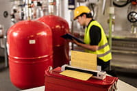 Engineer wearing yellow hard hat and high-vis vest kneeling down with clipboard, with Brother DSmobile DS-940DW portable document scanner in enginnering room