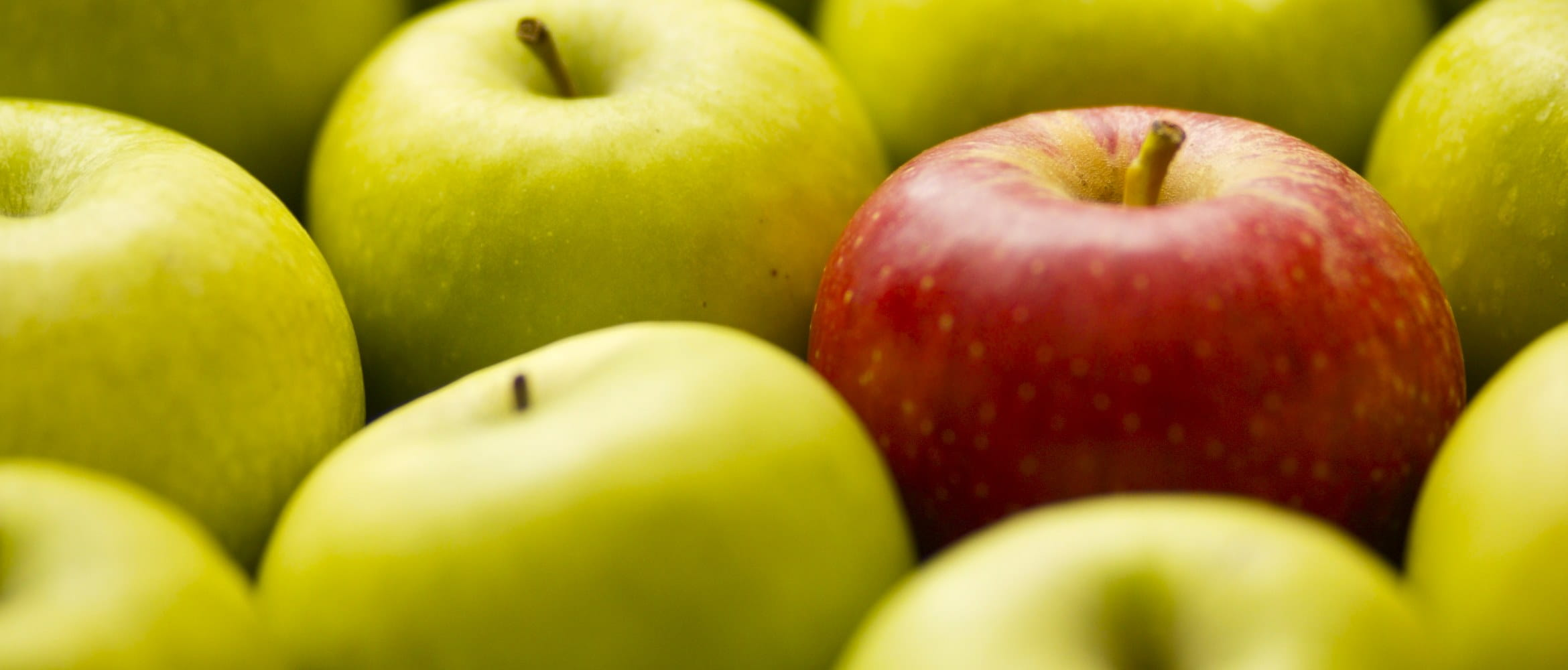 One red apple stands out against a selection of green apples in a grocery shop fruit basket