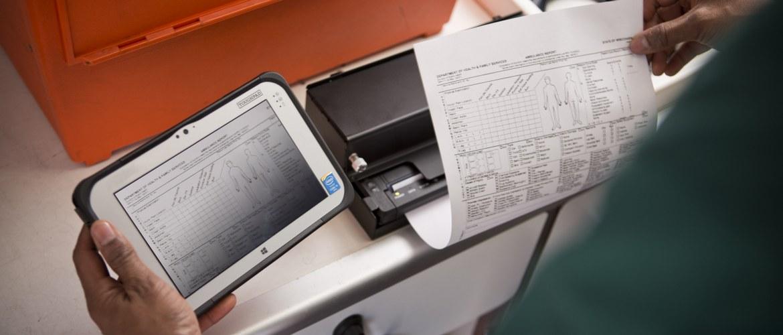 En helsearbeider med et nettbrett i en ambulanse skriver ut et dokument på en mobil skriver i Brother PJ700-serien