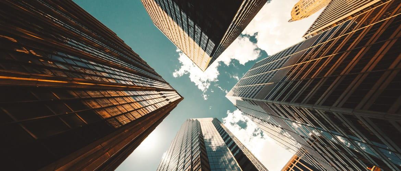 Kontor for fremtiden som skildrer skyskrapere i et bykvarter fra bakken og ser opp til himmelen