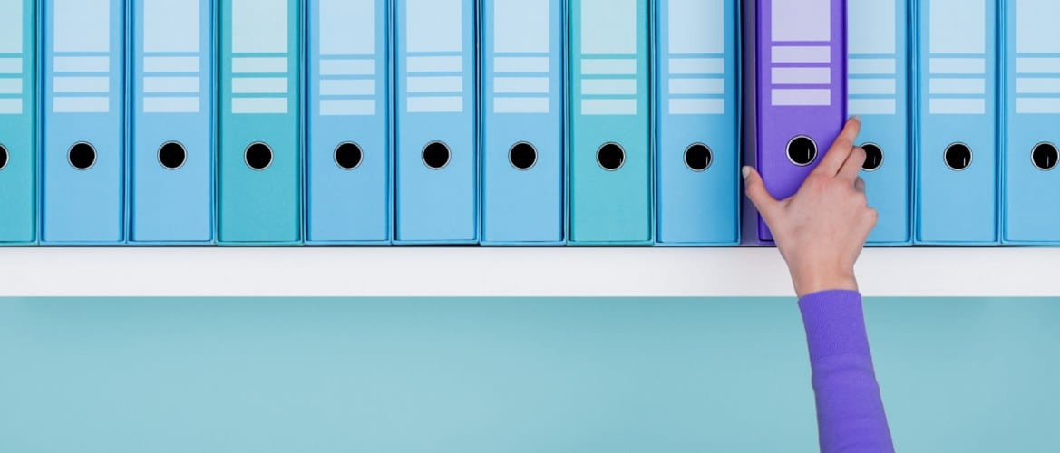 A shelf full of similar looking teal blue-green lever arch files has one purple file folder standing out. It is being picked up by an office staff member wearing a matching purple item of clothing.