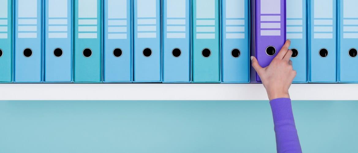En hylle full av blågrønne ringpermer har en lilla ringperm som skiller seg ut. Den blir tatt ut hyllen av en kontormedarbeider som har på seg en matchende lilla genser.