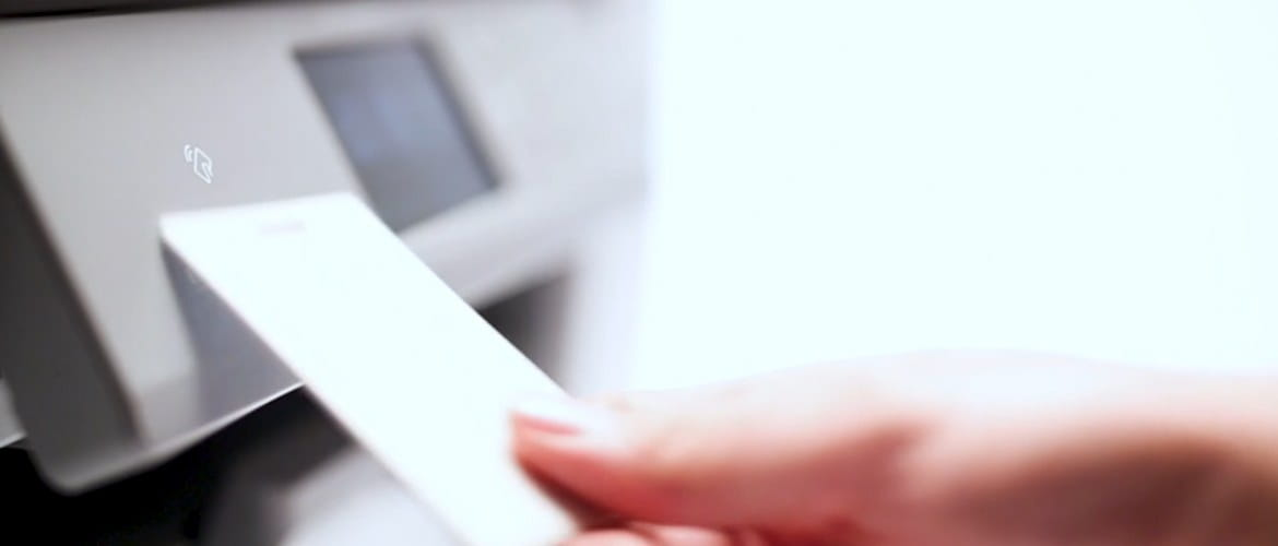A close up of a hand scanning a unique ID card to a printing device to print securely