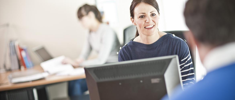 Kvinna jobbar med datorn och ler mot kollega