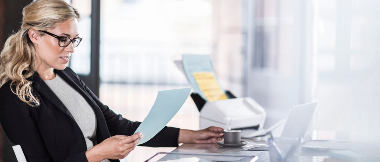 Dame sitter ved en kontorpult med en skanner og leser et dokument