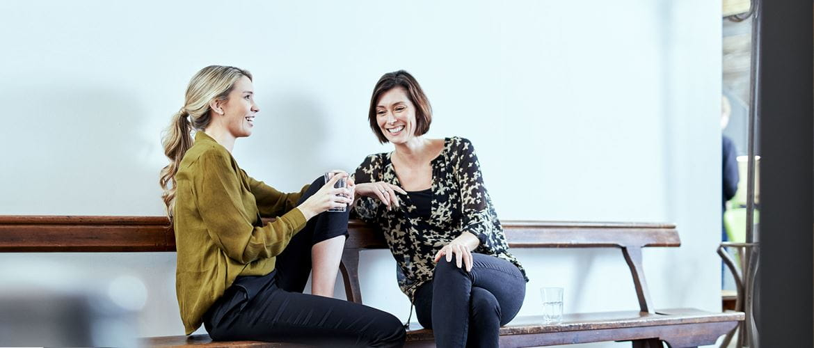 Two relaxed, laughing women sit talking on a bench