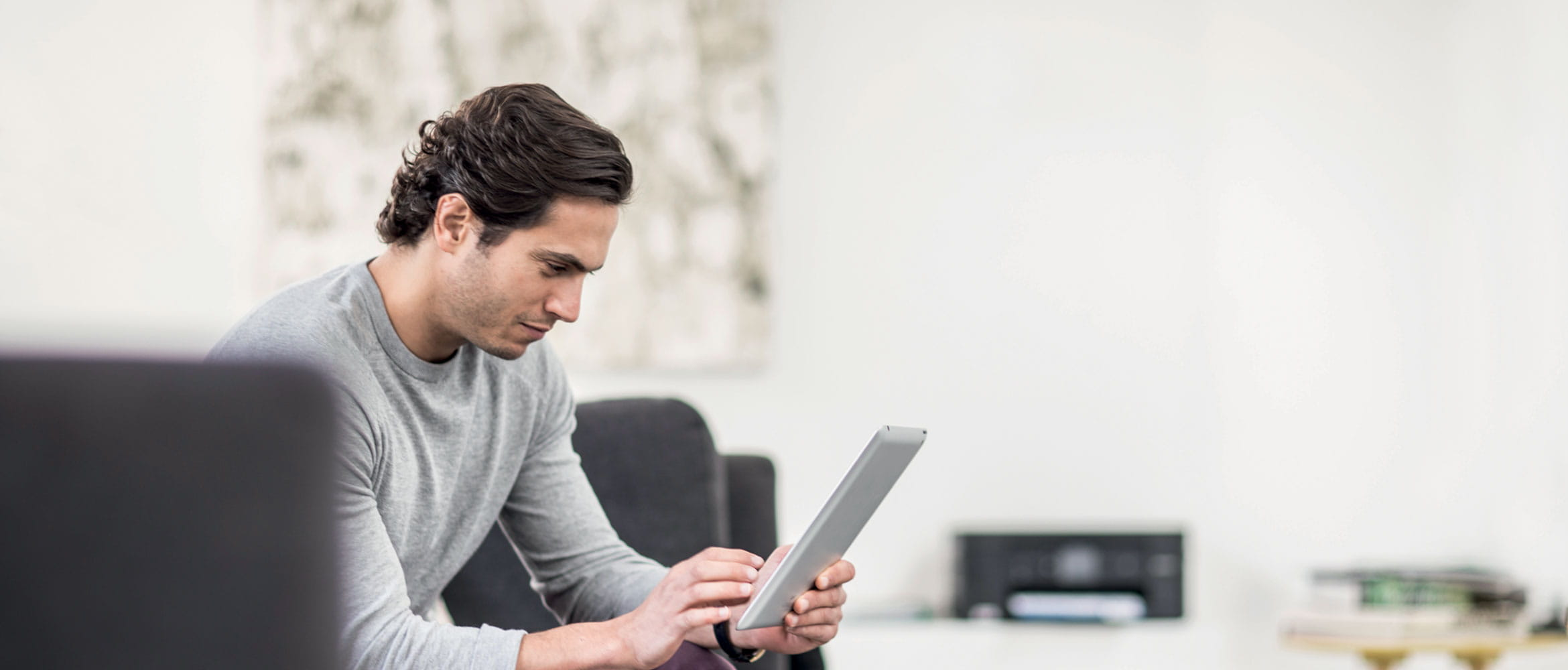 Man looking at tablet sat on sofa in home, with Brother printer in the background