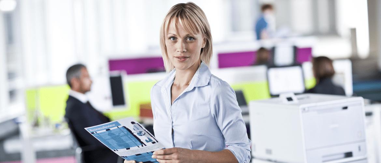 Kvinna håller en färgutskrift på ett kontor med en Brother laserskrivare bakom sig