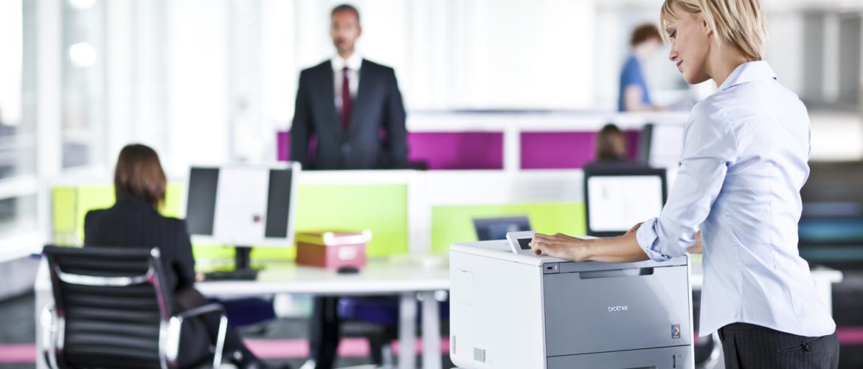 En kvinne på et kontor står ved en Brother laserskriver
