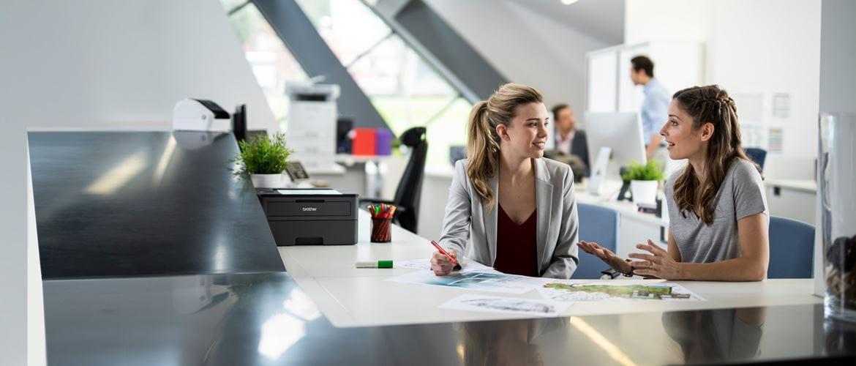 To kvinder, der sidder i et travl kontor og taler.