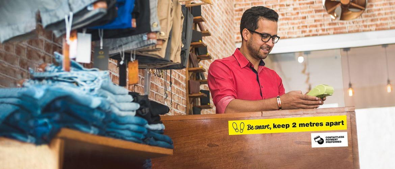 mann i kassen i en butikk og skilting som ber om kundene holde avstand