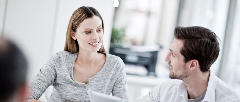 Mann og kvinner foran laptop smiler, skriver i bakgrunnen