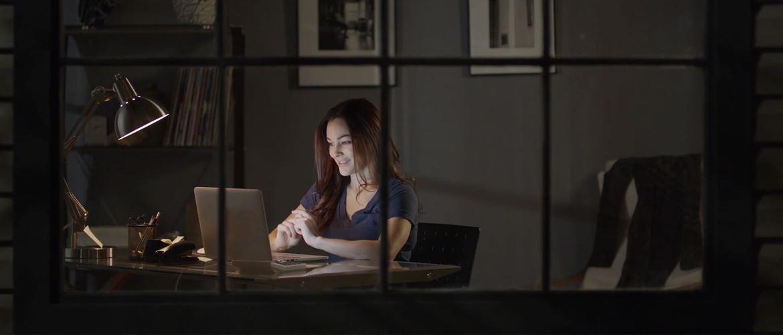 Nainen istuu läppärinsä ääressä illalla