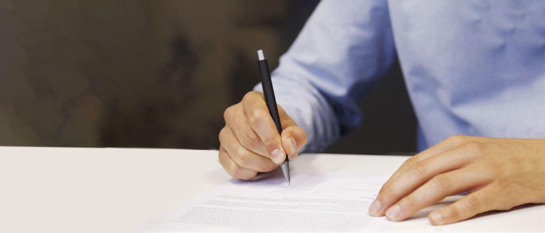 En mann med blå skjorte signerer et dokument