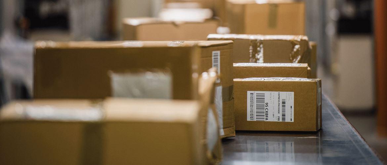 Pappesker på et transportbånd merket med leveranseetiketter med strekkoder