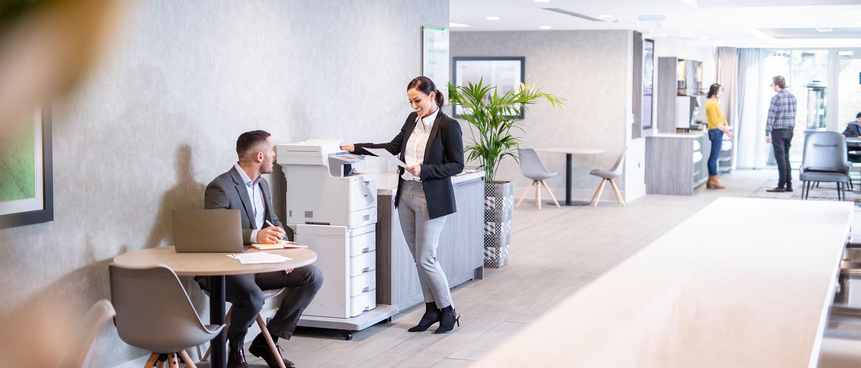 Moteris vilkinti kostiumą stovi prie Brother MFC-L9570CDWTT daugiafunkcinio spalvoto lazerinio spausdintuvo, vyras vilkintis kostiumu sėdi prie stalo su nešiojamuoju kompiuteriu, augalas, žmonės fone
