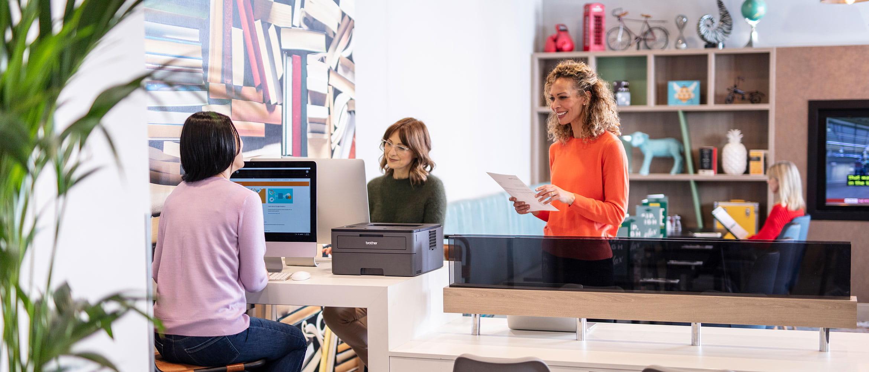 Två kvinnor som arbetar på datorer och kvinna som med orangea kläder på ett kontor
