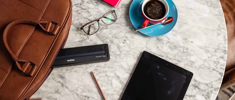 Rudas krepšys su rankena, Brother PJ mobilus pausdintuvas, pieštukas, planšetinis kompiuteris, kavos puodelis su kava, užrašinė