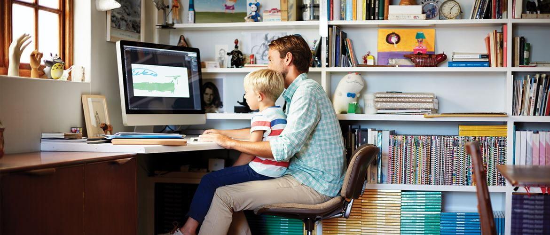 En far med sin sønn på fanget sitter foran datamaskinen på hjemmekontoret