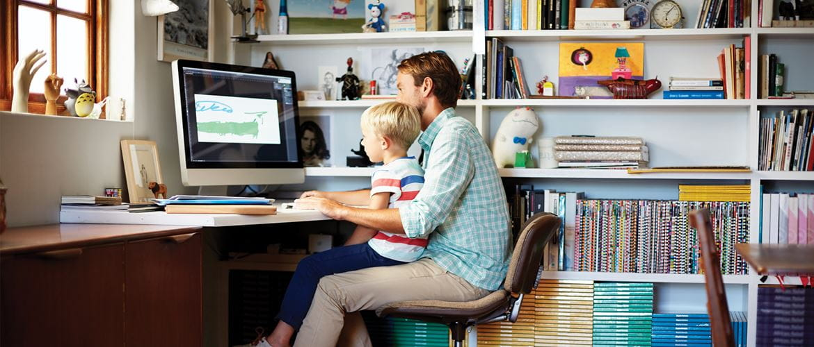 father and son sat desk working