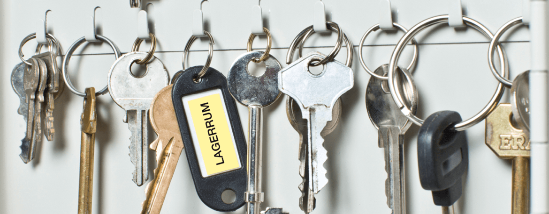 Nøkler som henger på en nøkkeltavle hvor en nøkkel er merket med en merkelapp