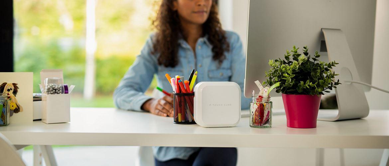 En kvinne sitter ved skrivebordet med en Brother P-touch CUBE merkemaskin for merkelapper og silkebånd
