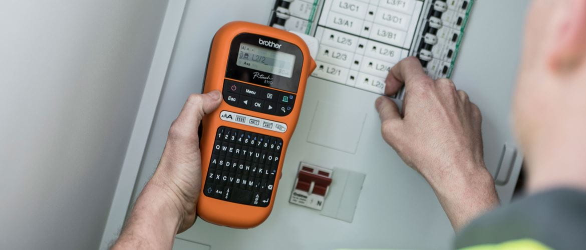 Electrician holding a mobile label printer next to fuse box