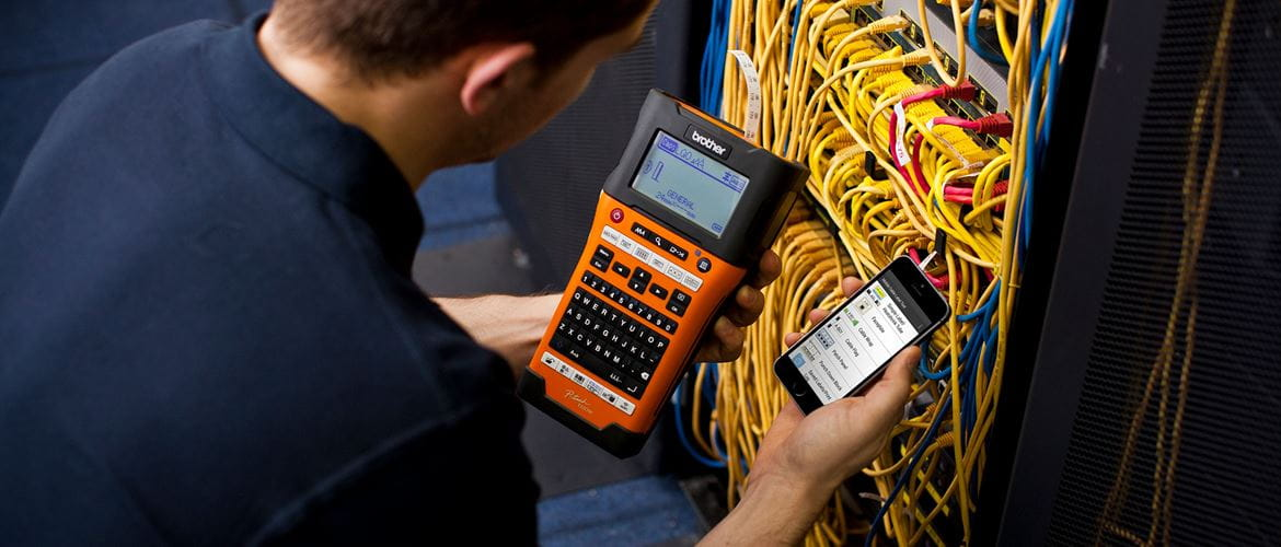Network technician using the Brother PT-E550WNIVP label printer with the Brother Mobile Cable Label Tool app to create labels for his network infrastructure