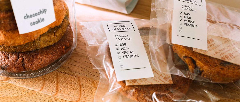 Kjeks i glassmugge med etiketter med sort og hvit skrift, to pakker med kjeks i plastposer med etiketter med sort og hvit skrift