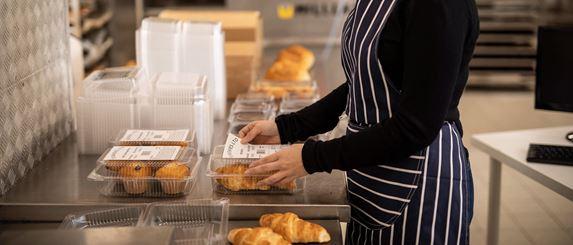 Nainen kiinnittää kroisantti- ja muffinssipakkauksiin tuotetietoja.