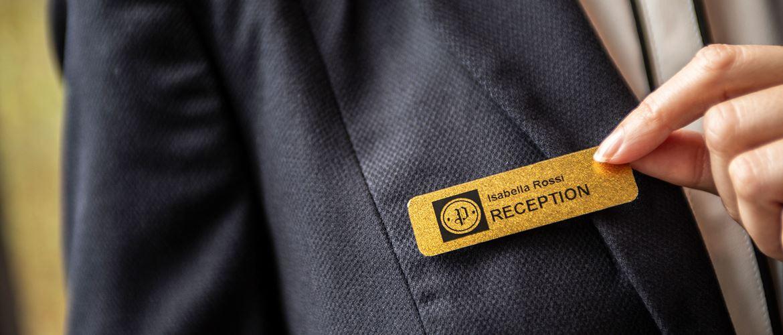 Hotellin vastaanottovirkailijalla on nimikyltti, jossa on tarramerkintä kultaisella taustalla ja mustalla tekstillä