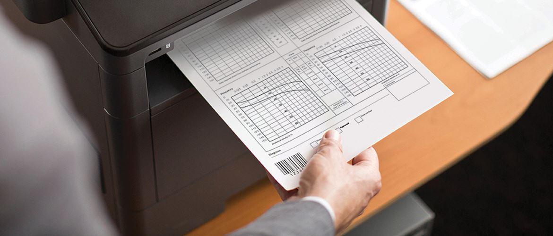 En person holder i et dokument som blir printet på en Brother skriver