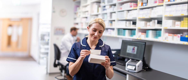 En ansatt på et apotek fester en etikett på en eske