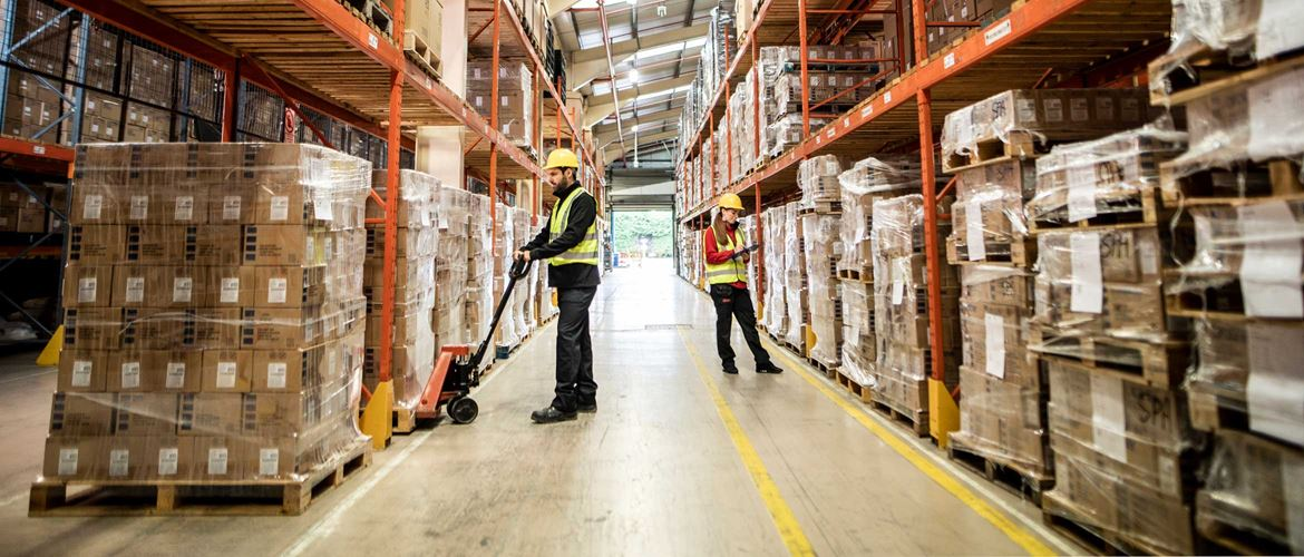Man and woman working in warehouse, pump truck, pallets, orange racking