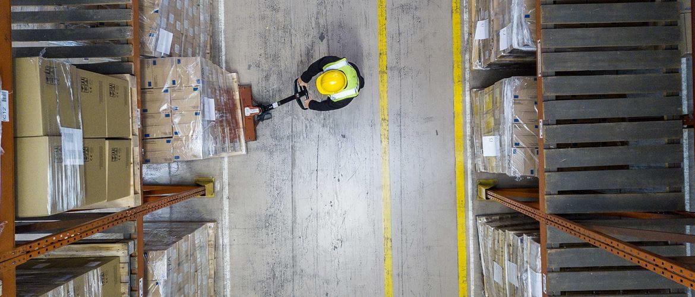 En lagermedarbeider med gul hjelm og vest flytter en pall med esker med en palletralle