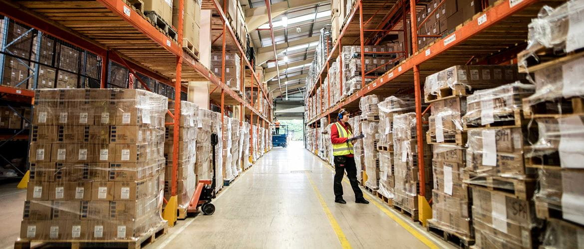 Female warehouse and distribution centre worker in his-vis holding clipboard in warhouse, boxes, orange racking
