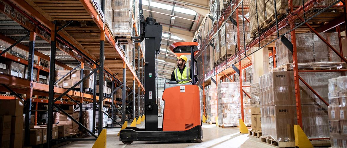 Man driving orange fork lift moving pallet from racking in warehouse and distribution centre